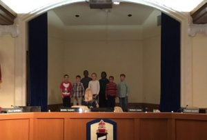 Student perform on stage during a School Board Meeting